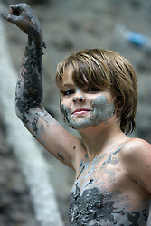 Young boy covered with mud