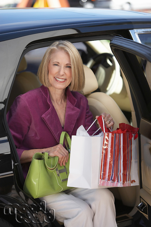 Woman with Shopping Bags Seated in Car