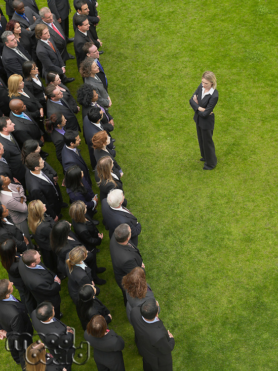 Business woman facing large group of business people in formation elevated view