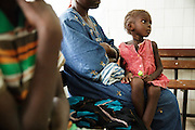 A girl sits on her mother's lap at the Koumassi general hospital in Abidjan Cote d'Ivoire on Friday July 19, 2013.