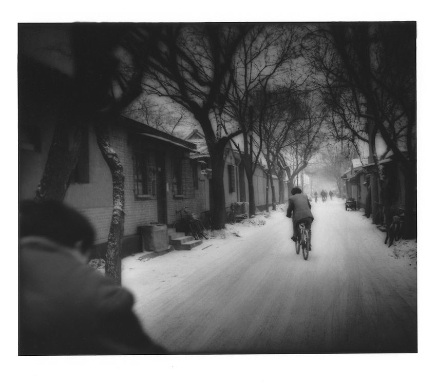"""Cyclists wind their way through a snowy """"hutong"""" (alley), Beijing, China."""