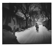 "Cyclists wind their way through a snowy ""hutong"" (alley), Beijing, China."