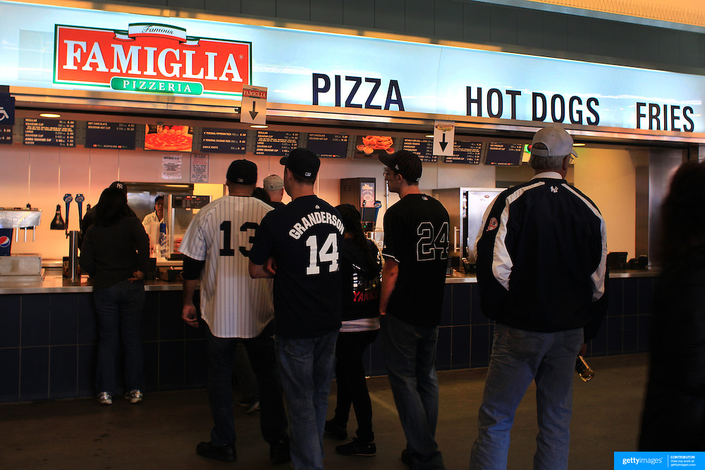 Fans queue for fast food pizza, hotdog and fries inside Yankee Stadium during the New York Yankees V Detroit Tigers Baseball game at Yankee Stadium, The Bronx, New York. 28th April 2012. Photo Tim Clayton
