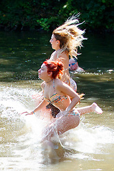 © Licensed to London News Pictures. 05/07/2017. London, UK. People jump into Hampstead Heath Mixed Bathing Pond in north London as temperatures hit 28C degrees on 5 July 2017. Photo credit: Tolga Akmen/LNP