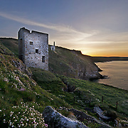 Wheal Trewavas Mine is at Rinsey near Porthleven. Seen in Poldark series. It is on the southern end of the granite outcrop known as the Godolphin-Tregonning Granite<br /> <br /> 1834 Wheal Trewavas opened. A plan of the time shows four copper lodes and one tin lode. The south east copper lode continued out under the sea and a small pumping engine and a steam whim were built on the south lode. Ore was carried to the cliff top by a horse whim. The sett of Wheal Trewavas contains four main copper lodes running generally in a NW-SE direction. They are North Lode; Sowan Way Lode; Trewavas South (or Old) Lode and Nimble Cutter Lode. These are intersected by the Great Tin lode running east to west across them. A pumping engine was installed on Old Engine shaft working the Old (South) Lode.<br /> <br /> 1838 a new pumping engine house housing a 45-inch cylinder was erected a few hundred metres to the east -on slightly higher ground - over New Engine (or Rogers') shaft.<br /> <br /> 1846 Wheal Trewavas closed. There was a suspicion that the dividends were being paid out of bank overdrafts.<br /> <br /> 1840's the mine employed around 200 people in mining and ancillary trades at Wheal Trewavas. A new shaft was sunk on the eastern section of the sett with a 70-inch pumping engine replacing the smaller engine on New Engine Shaft. This new shaft known as Diagonal shaft reached a depth of nearly 600 feet in the mid 1840'sl. It is known to have employed about 160 people around about this time.<br /> <br /> In the years Wheal Trewavas was in operation it produced over £100,000 worth of copper ore.<br /> <br /> The two engine houses still exist as the remains of Wheal Trewavas A circular flat area beyond the boiler house is one of Cornwall's best surviving 'manual capstan plats' and it is regularly used by helicopter pilots from Culdrose for landing practice.