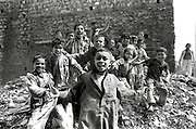 Jumping and yelling crowd of 15 pre-adolescent boys in a Cairo slum enthusiastically greet the photographer on a pile of rubbish near a building wall.  Their positions form a rough pyramid in front of the plain dark stone wall, and their eager grins set a cheerful note.  Mostwear striped pajamas as their day wear.