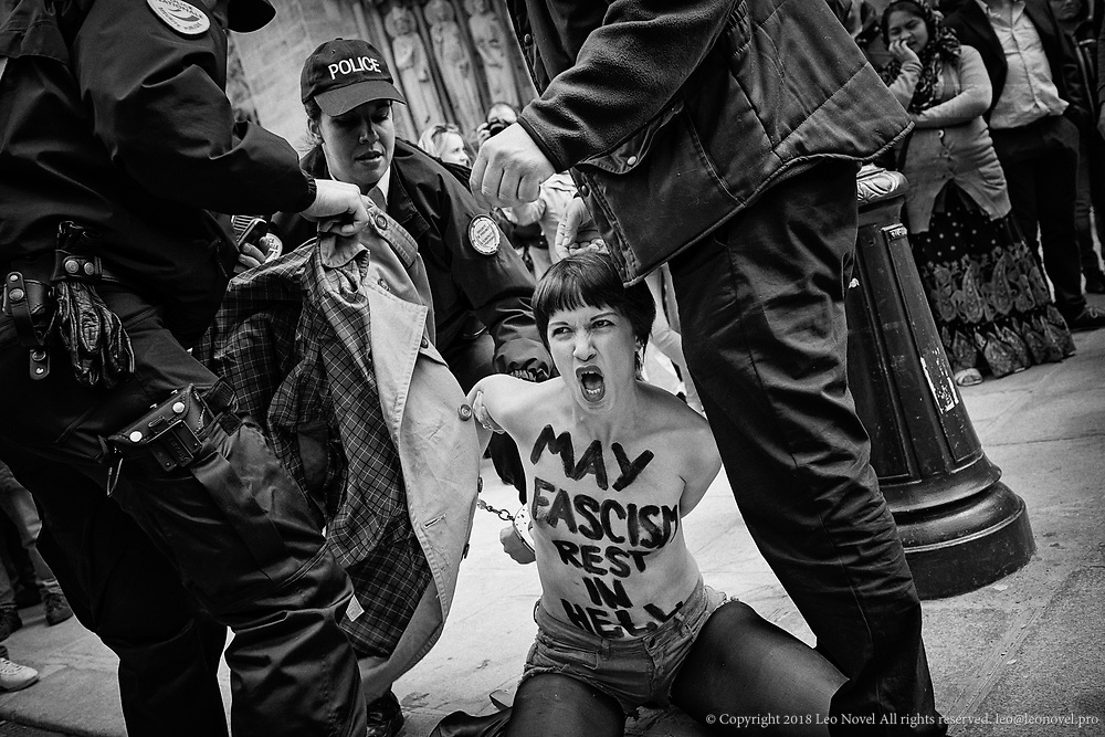 Marguerite Stern, a Femen member being arrested  after a topless protest in front of Notre Dame cathedral in Paris. The day before an extremist catholic author had committed suicide at the same place to show the discontent over legislation of french gay marriage law.