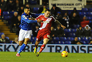 David Davis gets to grips with Le Tomlin during the Sky Bet Championship match between Birmingham City and Middlesbrough at St Andrews, Birmingham, England on 18 February 2015. Photo by Simon Kimber.