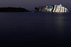 """18.01.2012, Insel, Giglio, ITA, Schiffsunglueck Costa Concordia, im Bild das Kreuzfahrtschiff Costa Concordia. Die gefährliche Suche nach Eingeschlossenen in dem gekenterten Kreuzfahrtschiff """"Costa Concordia"""" ist ins Stocken geraten. Aus Sicherheitsgründen wurde der Einsatz am Mittwoch unterbrochen, weil das Wrack weiter abgesunken war und in die Tiefe zu rutschen drohte. Nach einer ersten Vernehmung äußerte eine Untersuchungsrichterin harsche Kritik am Verhalten des Kapitäns Francesco Schettino. Der 52-Jährige selbst erzählte eine neue Variante des Geschehens in der Unglücksnacht. Demnach fiel er versehentlich in ein Rettungsboot, als er bei der chaotischen Rettungsaktion an Bord strauchelte. // .The cruise ship Costa Concordia leans on its side after running aground (on January 13) the tiny island of Giglio, Tuscany, Italy. EXPA Pictures © 2012, PhotoCredit: EXPA/ Insidefoto/ ARK/ Sebastian Seglingen ***** ATTENTION - for AUT, SLO, CRO, SRB, SUI and SWE only!"""