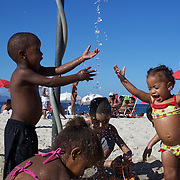 Young children play with a beach shower at Copacabana beach, Rio de Janeiro,  Brazil. 4th July 2010. Photo Tim Clayton..