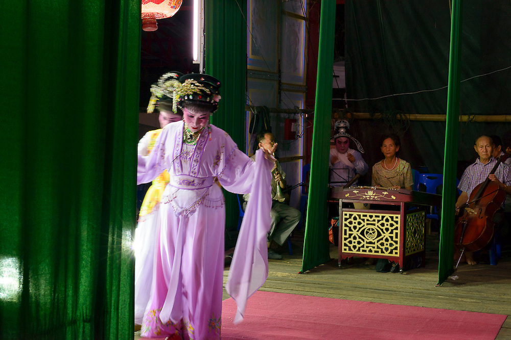 Singers and musicians of the Nam Sin Opera Company are seen from a backstage perspective.