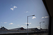 Clouds and station lamp posts seen from the window seat of a waiting train, on 2nd October 2019, in London, England.
