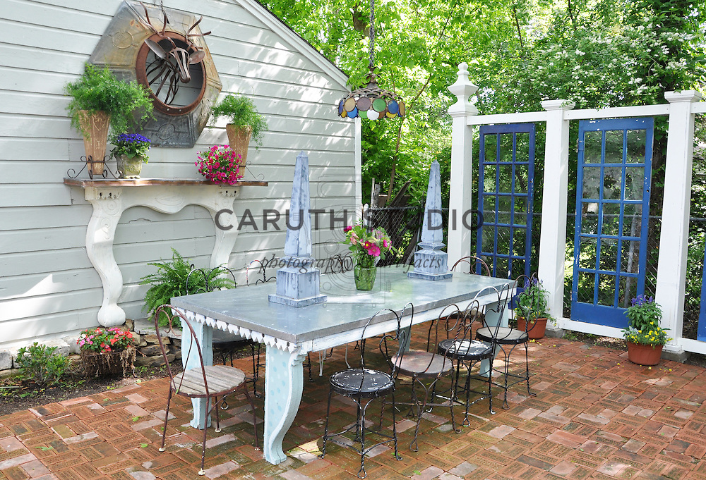Vintage garden: Brick patio with dining table, chairs, and screen made from architectural salvage