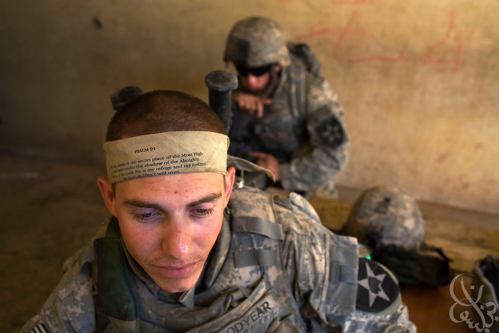 U.S. Army 1-23 Stryker Specialist Paul Goodyear from Chicago, IL wears a headband bearing a scripture passage during June 24, 2007 operations in Baquba, Iraq. U.S. and Iraqi soldiers continuing to search house to house in Baquba Iraq are finding numerous abandoned buildings rigged with explosives left behind by fleeing Al Qaeda fighters.   ...