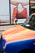 Lady shopper walks past a London taxi and womens' bag accessory retailer hoarding in Bond Street, London.