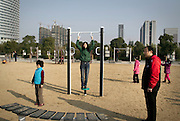 A Chinese family spend a sunny afternoon in a new municipal exercise park in a new city on the outskirts of Hefei.