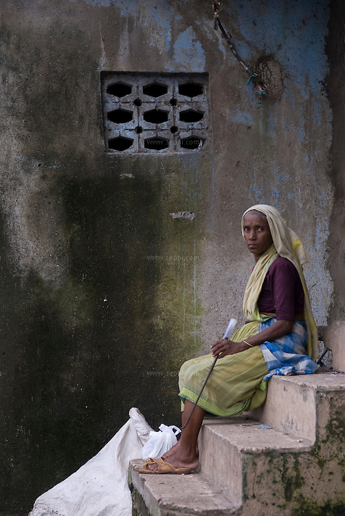 A rag-picker taking a rest from her work on the streets of Dharavi. Mumbai, August 2007