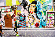 11 year old girl walking past section of the ever-changing graffiti in Hosier Lane, Melbourne, Australia