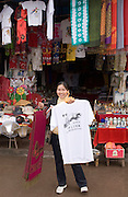 Souvenir seller selling t-shirts and scarves to passing tourists in Fengdu, China