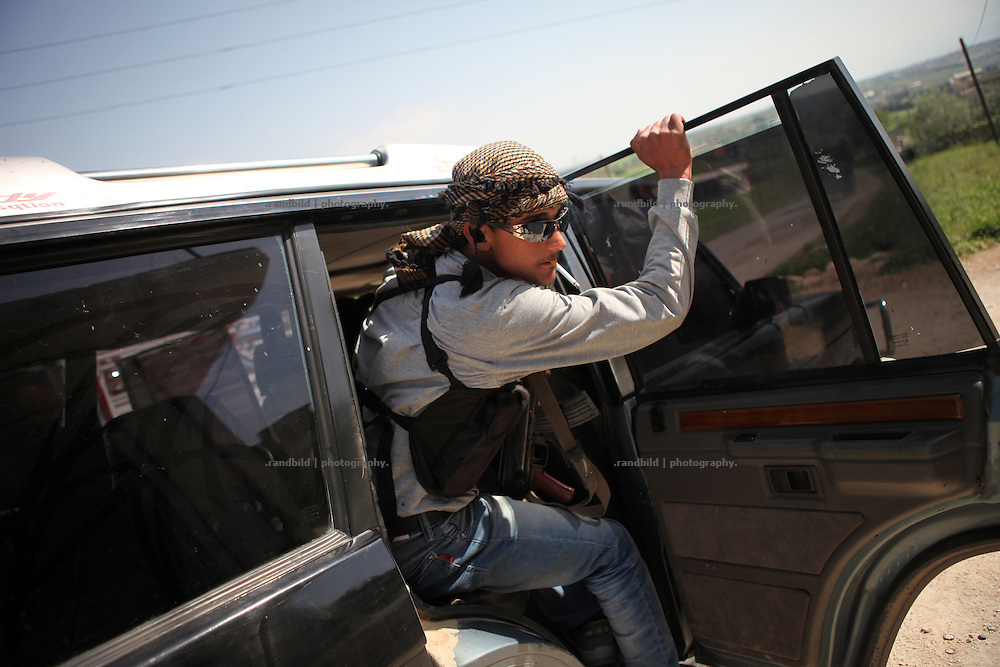 A young free syrian army member jumps into a rebell jeep with cigarette between his lips and a Kalashnikov in his hand.
