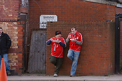 LIVERPOOL, ENGLAND - Saturday, January 26, 2008: Two Liverpool supporters eat traditional fish & chips outside Anfield. (Photo by David Rawcliffe/Propaganda)