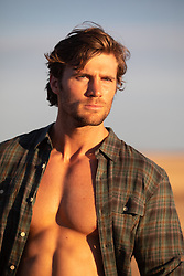 sexy man with open shirt outdoors at sunset