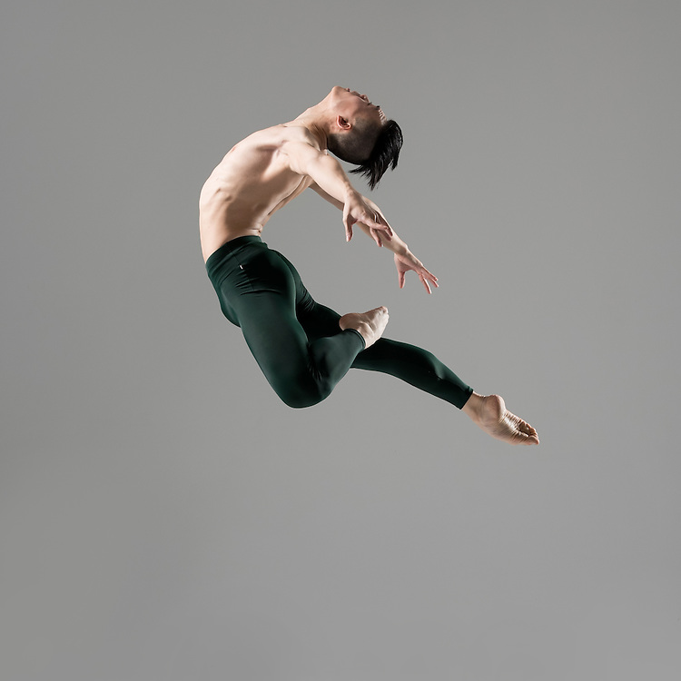 Classical male ballet dancer, Kevin Zong, jumping in the photo studio on a gray background. Photograph taken in New York City by photographer Rachel Neville.