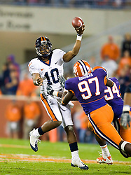 November 21, 2009; Clemson, SC, USA; Virginia Cavaliers quarterback Jameel Sewell (10) throws while being pressured by Clemson Tigers defensive tackle Rennie Moore (94) and defensive end Malliciah Goodman (97) during the fourth quarter at Memorial Stadium.  Clemson defeated Virginia 34-21.