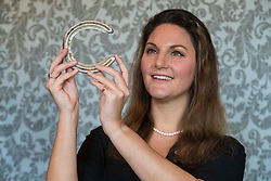 Charlotte Canby, Sporting Specialist at Bonhams with a racing plate worn by Frankel at the Royal Lodge Stakes Ascot in 2010 at the Bonhams Sporting Sale. Bonhams Sporting Sale will take place on 31 October at the Edinburgh auction rooms and will include a racing plate worn by the legendary racehorse Frankel (estimate £15,000 - £20,000), a large pair of Irish Elk antlers (estimate £15,000-20,000) and a cast of the British Record Salmon caught by Miss Ballantine in 1922 (estimate £3,000-5,000).