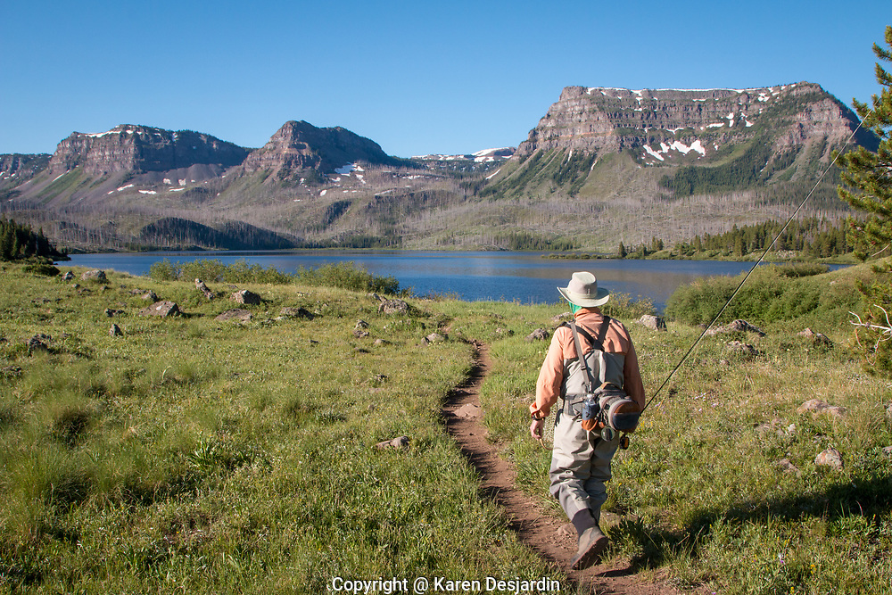A fly fisherman hikes toward Trappers Lake on a summer morning. Trappers Lake is in the Flat Tops Wilderness Area of northwestern Colorado.