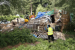 © Licensed to London News Pictures. 23/06/2017. Dorking, UK. Workers dismantle a protest  fort built over an oil well site near Leith Hill in the North Downs . Planning permission for 18 weeks of exploratory drilling was granted to Europa Oil and Gas in August 2015 after a four-year planning battle. The camp was set up by protestors in October 2016 in order to draw attention to plans to drill in this Area of Outstanding Natural Beauty (AONB) in the Surrey Hills. The camp has received support from the local community. Photo credit: Peter Macdiarmid/LNP