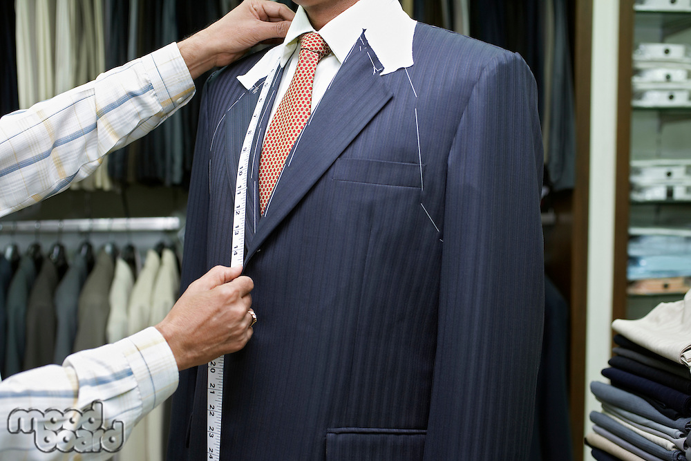 Tailor measuring business man for suit mid section