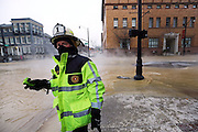 Columbus Fire Battalion Chief Michael Fowler radios to firefighters on Gay Street as the crews deal with a 24-inch water main that burst open in the middle of North 4th and East Gay streets in downtown Columbus just before rush hour on Jan. 6, 2014. Traffic was shut down on 4th street between Broad and Spring streets. (Adam Cairns / The Columbus Dispatch)