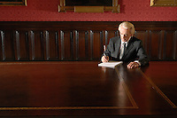 Man sitting in Board Room writing