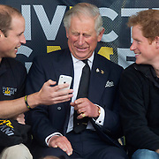 Britain's Princes William, Charles, and Harry look at a phone during the Invictus Games in Lee Valley athletics stadium in north London September 11, 2014 REUTERS/Neil Hall