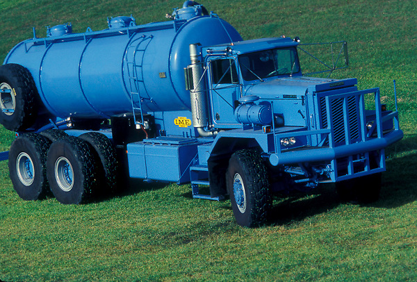 Large blue liquid transportation truck parked in a field of grass