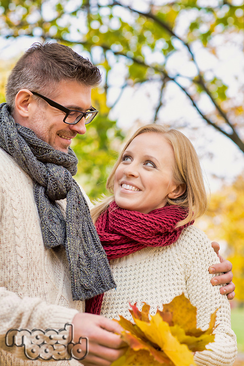 Portrait of mature couple holding maple leaves in park