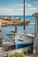 Formentera, Spain, October 2017. Traditional boat houses and  boats in the fishing village of Es Calo. Formentera is the smallest of Spain's Balearic islands in the Mediterranean Sea. It's reachable by ferry from its more crowded, better known island neighbor, Ibiza, and makes for a popular day-trip destination in the summertime. It's known for its clear waters and long stretches of beach backed by dunes and pine trees. Pastimes include snorkeling and sailing, with equipment rentals and boat charters available. Photo by Frits Meyst / MeystPhoto.com