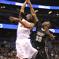 Florida Gators forward Alex Tyus (23) drives the ball past Keith Clanton (33) while playing against the University of Central Florida Knights  at the Amway Center on December 1, 2010 in Orlando, Florida. Central Florida won the game 57-54 for their first ever victory against a nationally ranked team. (AP Photo/Alex Menendez)