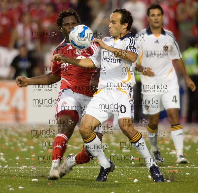 Los Angeles Galaxy's Landon Donovan(R) fights for the ball with Toronto FC's Alan Gordon  during their 05 August, 2007 in Toronto, Ontario, Canada. The match ended in a scoreless tie.  .AFP PHOTO/GEOFF ROBINS