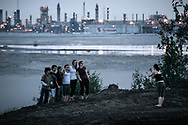 A Greenpeace activist takes a picture of a group touring, from the outside, the mining area.. In background, Syncrude's bitumen upgrader (bitumen has to be refine to oil before circulating in pipelines toward refinery) and a tailing pond that capture wasted water loaded with toxic wastes.   02 July 2008.