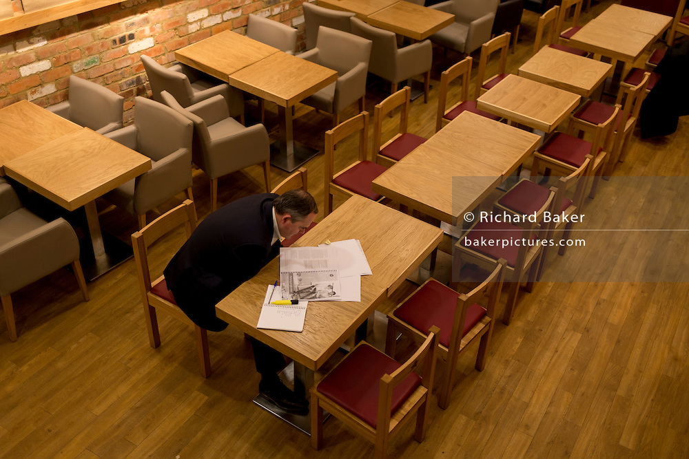 A businessman reads paperwork in a sandwich bar on 13th February 2017, in London, United Kingdom.