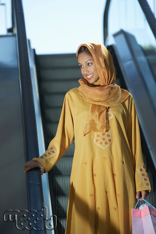 Young muslim woman on escalator