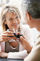Middle-aged couple sitting at outdoor cafe in Rome toasting wine glasses close up