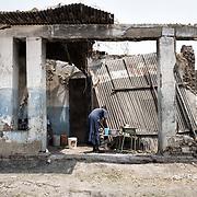 Une femme lave sa vaisselle dans les décombres d'une maison de Malakal. Avant le début de la guerre civile, en 2013, Malakal était la deuxième du pays, elle comptait plus de 150 000 habitants, principalement des Nuer et des Shilluk. Aujourd'hui, elle est essentiellement peuplée de soldats loyalistes et de leurs familles, principalement des Dinka.