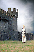 a woman in a white period dress is standing in front of a castle