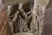 Carved capital depicting 2 men blowing horns and foliage decoration, in the galleries of the Abbatiale Sainte-Foy de Conques or Abbey-church of Saint-Foy, Conques, Aveyron, Midi-Pyrenees, France, a Romanesque abbey church begun 1050 under abbot Odolric to house the remains of St Foy, a 4th century female martyr. The church is on the pilgrimage route to Santiago da Compostela, and is listed as a historic monument and a UNESCO World Heritage Site. Picture by Manuel Cohen