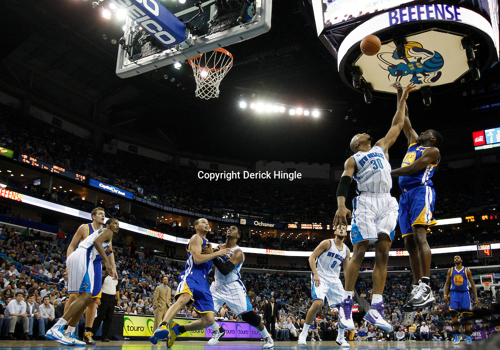January 5, 2011; New Orleans, LA, USA; Golden State Warriors power forward Ekpe Udoh (20) shoots over New Orleans Hornets power forward David West (30) during the fourth quarter at the New Orleans Arena. The Warriors defeated the Hornets 110-103.  Mandatory Credit: Derick E. Hingle
