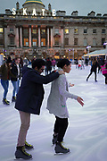 A nervous man hangs onto a young woman on the Christmas skating rink at Somerset House in central London, on 4th December 2017, in London England.