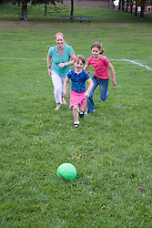 Mother and her daughters playing football in the park,
